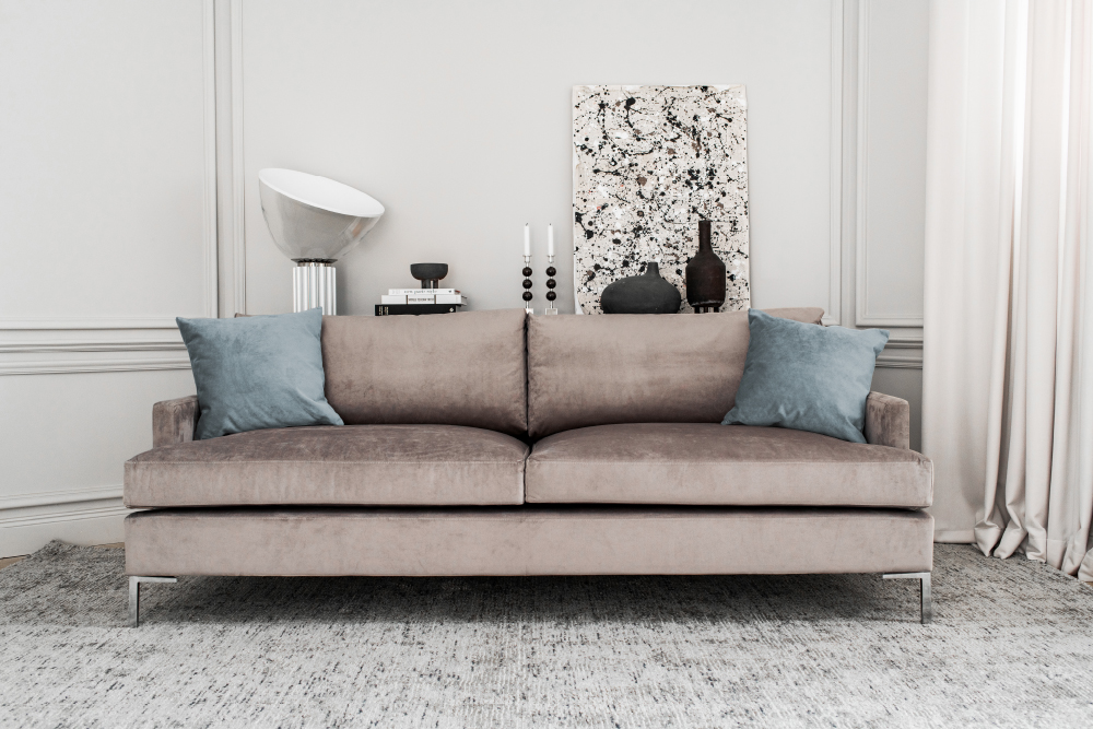 Layered modern elegant gray beige velvet sofa in posh home